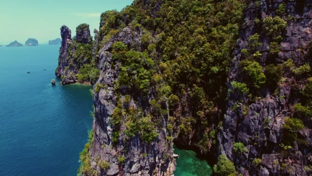 aerial of tropical sea cliffs in thailand - longtail boat stock videos & royalty-free footage