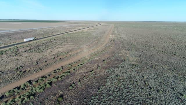 aerial of truck driving through outback desert landscape - ökenklimat bildbanksvideor och videomaterial från bakom kulisserna