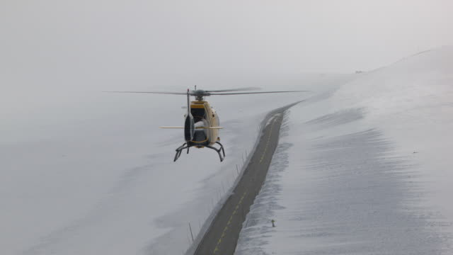 aerial of two helicopters flying in mountains in winter. - helicopter stock videos and b-roll footage
