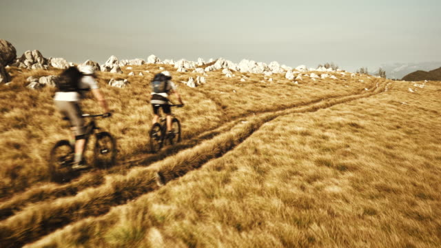 vídeos y material grabado en eventos de stock de vista aérea de dos ciclistas de montaña, pasando por ridge - mountain bike
