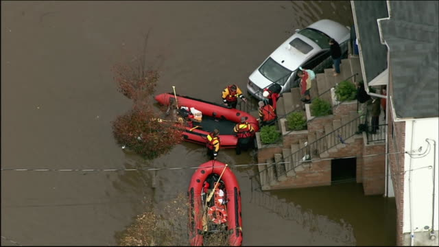 aerial of two rafts outside of home on flooded street zoom out zoom back to rafts outside of stairs residents walk down steps with belongings zoom... - environment or natural disaster or climate change or earthquake or hurricane or extreme weather or oil spill or volcano or tornado or flooding stock videos & royalty-free footage