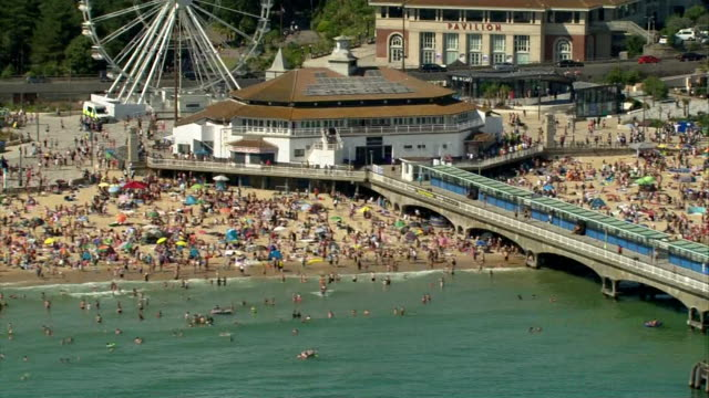 aerial of very crowded bournemouth beach in the heatwave during coronavirus lockdown crowds make it hard for social distancing to be observed - bournemouth stock-videos und b-roll-filmmaterial