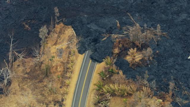 vídeos y material grabado en eventos de stock de aerial of volcanic lava rock lava blocking road - paisaje volcánico