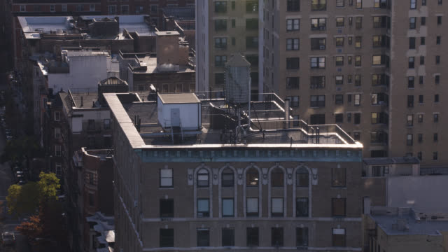 vídeos y material grabado en eventos de stock de aerial of water tank on rooftop of multi-story and high rise office or apartment buildings in upper west side manhattan new york city. - sección alta