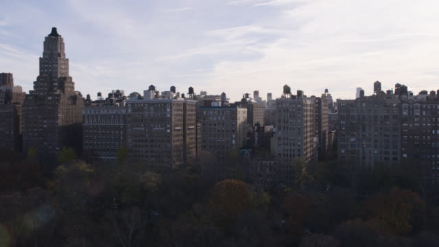 aerial of water tank on rooftop of multi-story and high rise office or apartment buildings in upper west side manhattan new york city. riverside park. - storage tank stock videos and b-roll footage