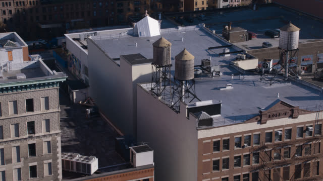 aerial of water tanks on rooftop of multi-story office or apartment buildings. harlem, new york.