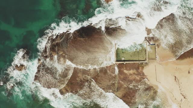aerial of waves und tidal pool. australien - gezeitentümpel stock-videos und b-roll-filmmaterial