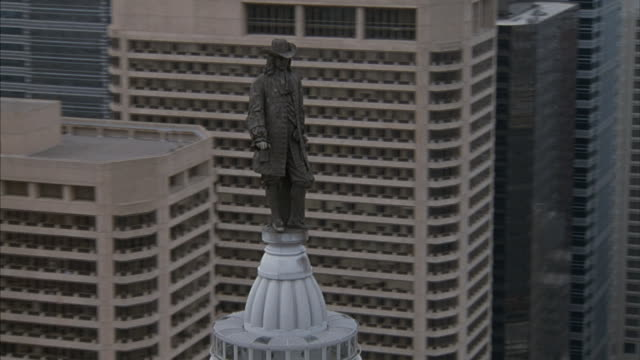 Aerial of William Penn statue atop Philadelphia's city hall and the city hall.