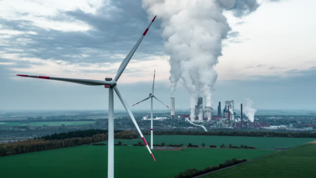 aerial of wind turbines and a coal power plant - coal stock videos & royalty-free footage