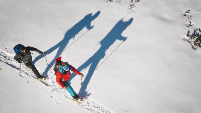 luftaufnahme von winter bergsteiger schneeschuhwanderungen über tal an einem sonnigen tag - winter stock-videos und b-roll-filmmaterial