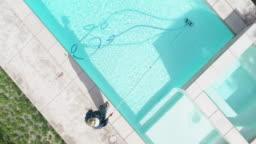 Aerial of Woman Vacuuming Swimming Pool
