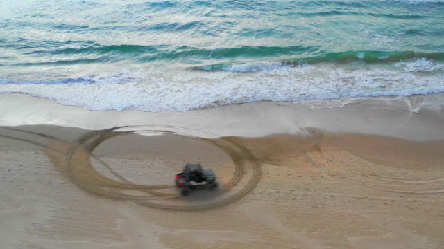 aerial: off-road vehicle doing donuts in the sand in caesarea, israel - doughnut stock videos and b-roll footage