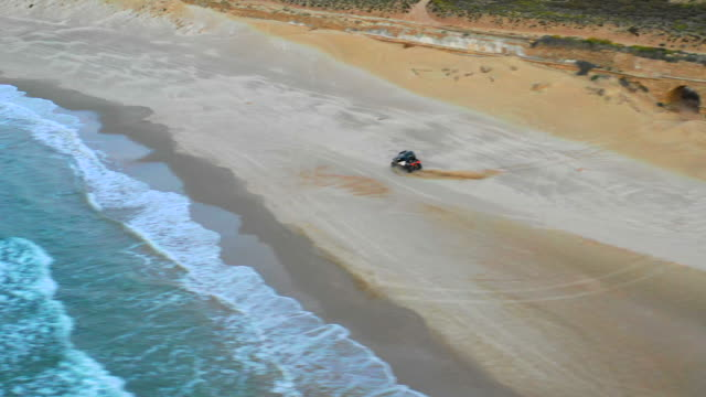 aerial: off-road vehicle doing donuts on the beach in caesarea, israel - caesarea stock videos & royalty-free footage