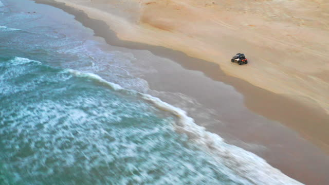aerial: off-road vehicle driving on the beach in caesarea, israel - caesarea stock videos & royalty-free footage
