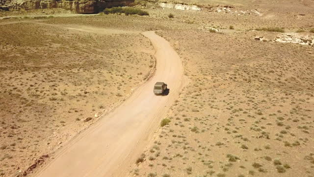 aerial: off-road vehicle moving on road amidst semi arid landscape during sunny day - page, arizona - öde landschaft stock-videos und b-roll-filmmaterial