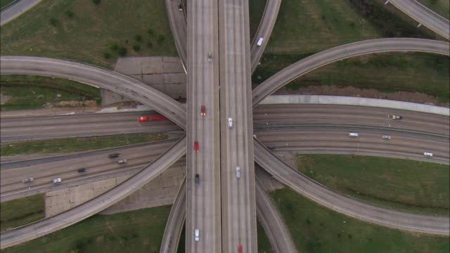 Aerial OH WS Traffic driving around highway interchange / Dallas, Texas, USA