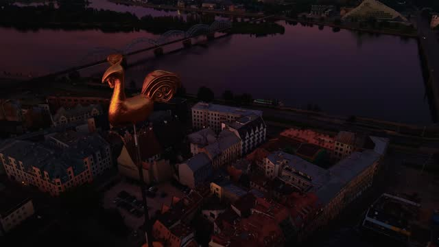 aerial orbit around golden weather cock or rooster in beautiful riga old town during amazing scenic sunrise aerial - state of the vatican city stock videos & royalty-free footage