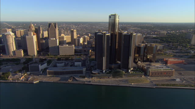 aerial ws ore carrier ship on detroit river passing general motors headquarters at renaissance center and downtown cityscape / detroit, michigan, usa - detroit river stock-videos und b-roll-filmmaterial