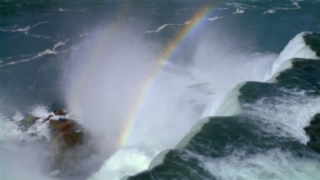 aerial over american falls with town in background / rainbow / niagara falls, new york - fluss niagara river stock-videos und b-roll-filmmaterial