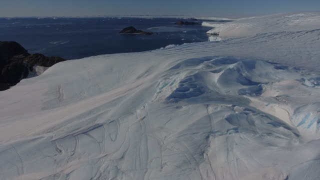 aerial over an ice shelve crevasse and rocks close to larsemann hills prydz bay between bharati and davis station in antarctica - antarctica sunset stock videos & royalty-free footage
