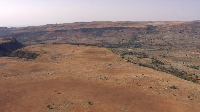aerial over arid hills and valley, madagascar - pianura video stock e b–roll