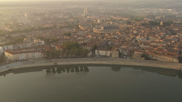 aerial over arles, france at sunrise,  the camera faces south and moves backward, seeing the sunrise on the left and arles amphitheatre just below. - amphitheatre stock videos & royalty-free footage