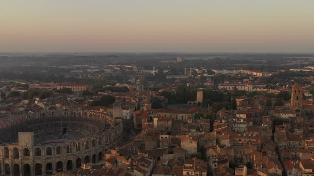 aerial over arles, france at sunrise while the camera starts over the river and moves forward and pans left toward the arles amphitheatre. - amphitheatre stock videos & royalty-free footage