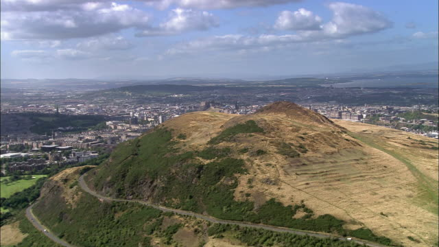 Aerial over Arthur's Seat to panoramic view of central Edinburgh / Scotland