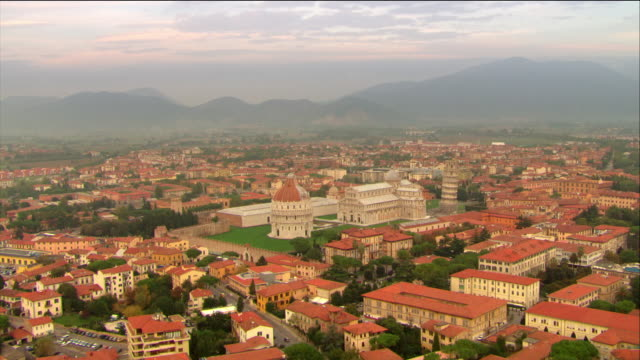 Aerial over baptistery, cathedral, Leaning Tower of Pisa, Camposanto and stadium / Pisa, Italy