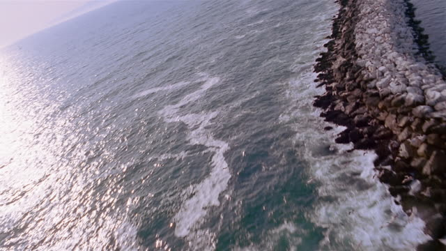 Aerial over birds flying over water / waves crashing against rock wall