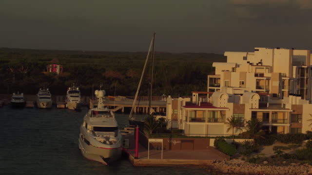 aerial over boats docked at a marina next to square, white hotels in cancun - quintana roo stock videos and b-roll footage