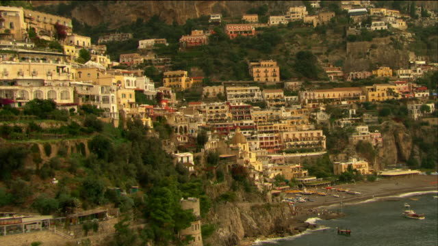 Aerial over buildings and residences on coast of Positano to boats on beach / Italy