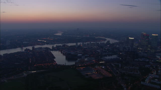 vídeos de stock e filmes b-roll de aerial over canary wharf along thames at dusk / london - hsbc towers