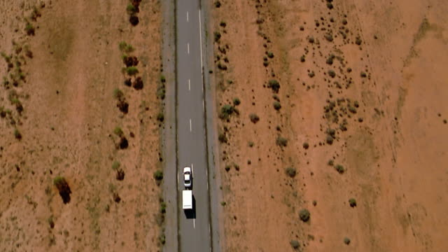 aerial over car pulling trailer on desert road - aerial view stock videos & royalty-free footage