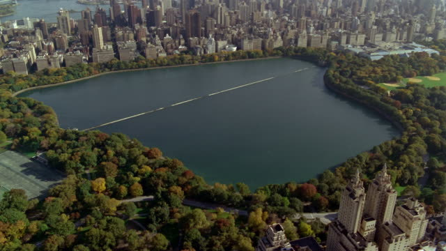 aerial over central park reservoir with buildings in background / new york city - central park reservoir stock videos and b-roll footage
