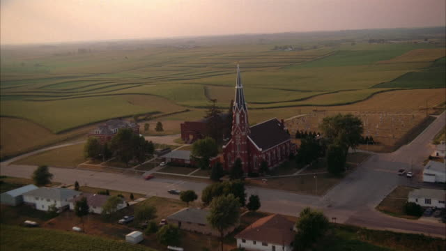 aerial over church with steeple, houses and cultivated fields in small town / iowa - kirche stock-videos und b-roll-filmmaterial