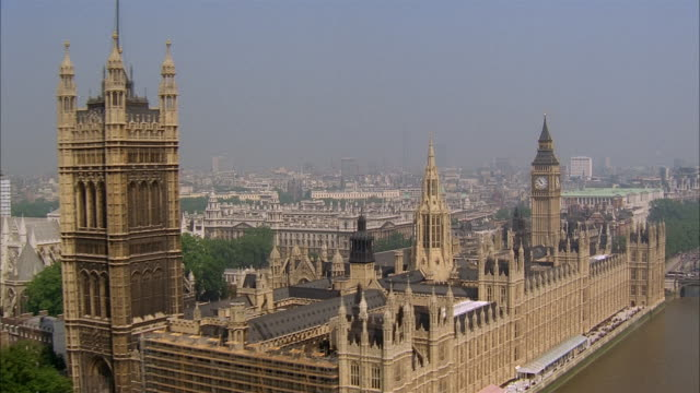 aerial over city of london past parliament building and big ben on foggy day / england - parliament building stock videos & royalty-free footage