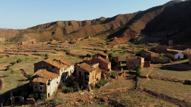 aerial over cluster of derelict houses and terraced landscape in abandoned village el campo, aragon - spanien stock-videos und b-roll-filmmaterial