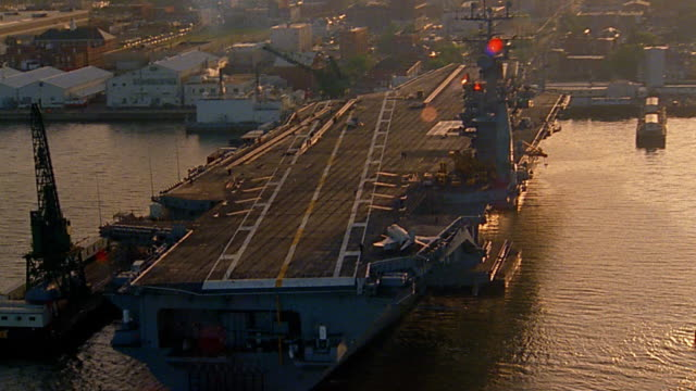 Aerial over docked aircraft carrier with fighter jet on deck / Norfolk, Virginia