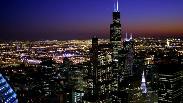 aerial pov over downtown chicago and past sears tower at night / illinois - torre sears video stock e b–roll