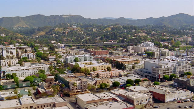 Aerial over downtown Los Angeles with Hollywood Hills in background