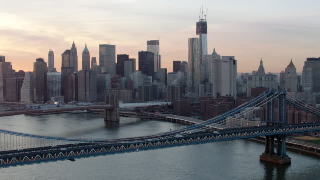 Aerial over East river of downtown Manhattan and bridges at sunset
