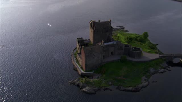 Aerial over Eilean Donan castle on loch, Scotland, UK
