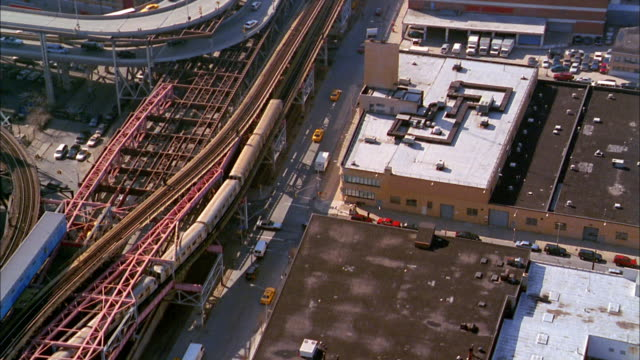 aerial over elevated subway train and rooftops / long island city, queens - 2000年点の映像素材/bロール