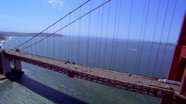 stockvideo's en b-roll-footage met aerial over entrance to golden gate bridge, fort point, and length of bridge / turning around over other end of bridge / san francisco bay, california - noordelijke grote oceaan