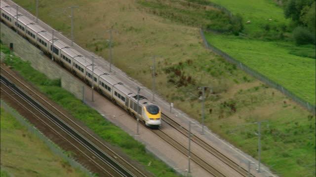aerial over eurostar train travelling along tracks / kent, england - eurostar stock-videos und b-roll-filmmaterial