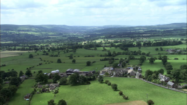 Aerial over farms, fields and hilly countryside, Yorkshire Dales, UK