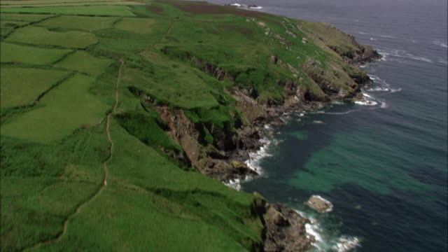 Aerial over fields, cliffs and sea, Cornwall, UK