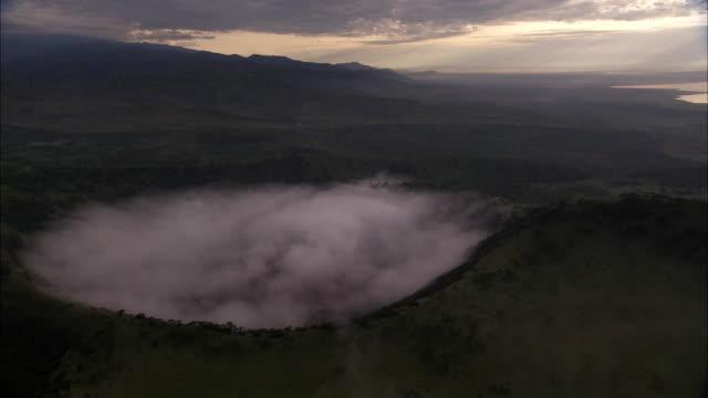 vídeos y material grabado en eventos de stock de aerial over forest and mist in extinct volcanic crater, uganda - volcán extinguido