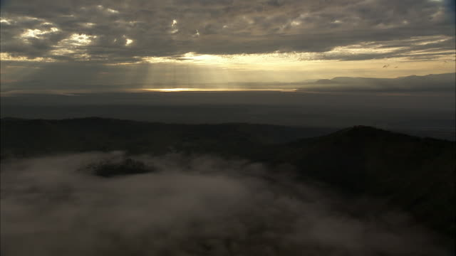 aerial over forest and mist in extinct volcanic crater, uganda - ドラマチックな空模様点の映像素材/bロール